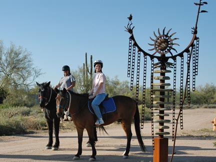 Riders on horses next to Mother Earth sculpture