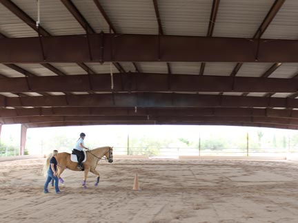 Student riding in covered arena, instructor walking beside
