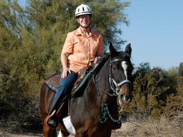 smiling woman in helmet riding horse