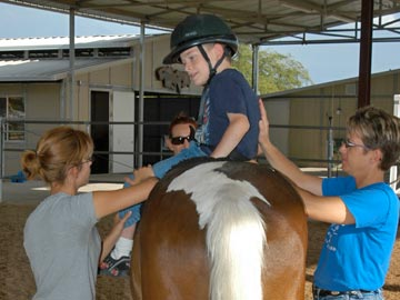 young boy student on horse with volunteers helping him dismount