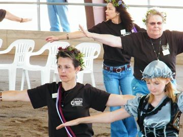 volunteers walking with arms outspread at Hooves and Heroes performance