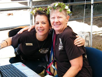 two smiling volunteers with flowered headresses hugging at Hooves & Heroes event