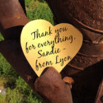 "gold heart with black script ""Thank you for everything, Sandie - from Lyon"" being held by rusty armor statue"