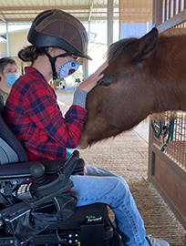 Student in a wheelchair in the barn aisle, wearing a face mask; Nutmeg's head is extended from her stall so that the student can pet her