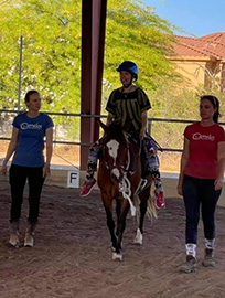 Nutmeg being ridden in the covered arena with 2 women walking beside her